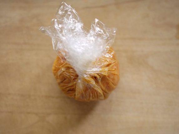 味噌をチーズで包むようにラップの上から伸ばしていく様子